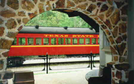 A car on the Texas State Railroad framed by the Palestine Station Arch